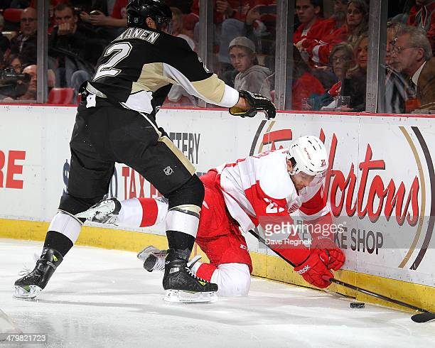 Matt Niskanen of the Pittsburgh Penguins knocks Tomas Tatar of the Detroit Red Wings off the puck during an NHL game on March 20 2014 at Joe Louis...