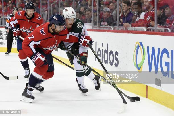 Matt Niskanen of the Washington Capitals and Ryan Donato of the Minnesota Wild battle for the puck in the second period at Capital One Arena on March...