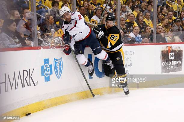 Matt Niskanen of the Washington Capitals and Sidney Crosby of the Pittsburgh Penguins slam into the boards while chasing after a loose puck during...