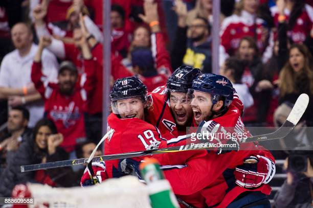 Matt Niskanen of the Washington Capitals celebrates with Tom Wilson and Nicklas Backstrom after scoring a third period goal against the New York...