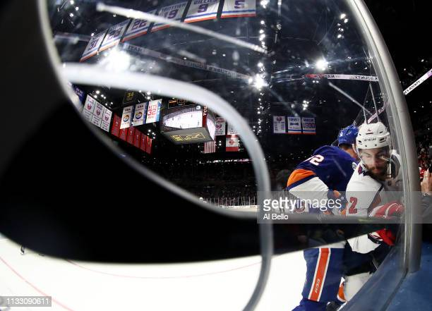 Matt Niskanen of the Washington Capitals is checked by Ross Johnston of the New York Islanders during their game at NYCB Live's Nassau Coliseum on...