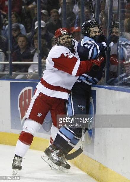 Matt Olinger of Wisconsin checks Josh Soares during 2nd-period action in the semi-finals of the NCAA frozen four at the Bradley Center in Milwaukee,...