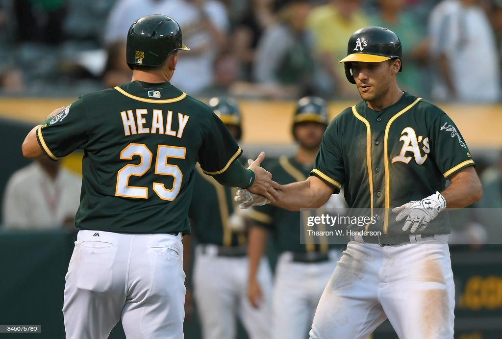Matt Olson #28 and Ryon Healy #25 of the Oakland Athletics celebrates after Olson hit a two-run homer against the Houston Astros in the bottom of the six inning of the second game in a double header at Oakland Alameda Coliseum on September 9, 2017 in Oakland, California.