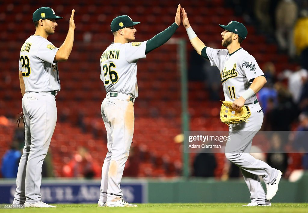 Matt Olson #28, Matt Chapman #26 and Dustin Fowler #11 of the Oakland Athletics high five each other after a victory over the Boston Red Sox at Fenway Park on May 15, 2018 in Boston, Massachusetts.