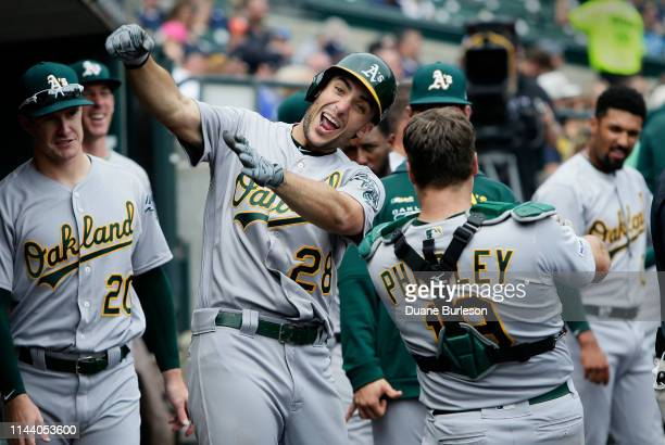 Matt Olson of the Oakland Athletics celebrates his solo home run against the Detroit Tigers with catcher Josh Phegley of the Oakland Athletics during...