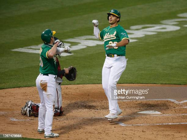 Matt Olson of the Oakland Athletics celebrates with Mark Canha after hitting a two-run home run in the bottom of the fourth inning against the...