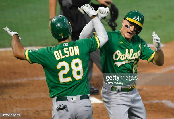 Matt Olson of the Oakland Athletics congratulates Matt Chapman on his two-run home run against the Los Angeles Angels in the third inning at Angel...