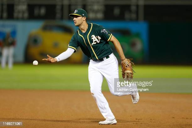 Matt Olson of the Oakland Athletics fields the ball and throws to first base to get the out of Austin Romine of the New York Yankees in the top of...