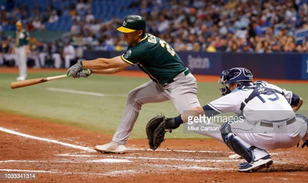 Matt Olson of the Oakland Athletics follows through on an RBI single in the fourth inning of a baseball game in front of Nick Ciuffo of the Tampa Bay...