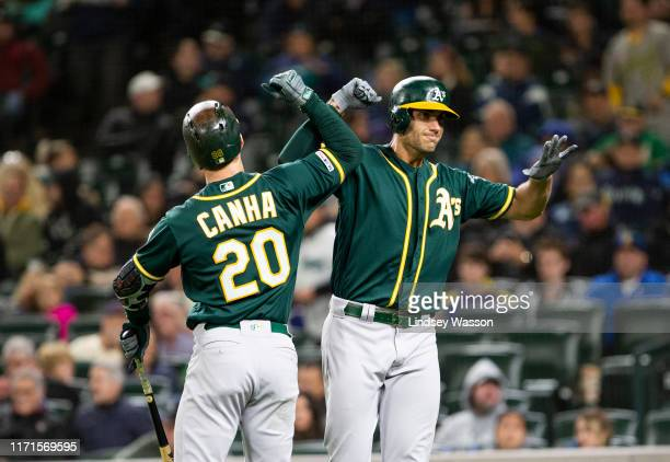 Matt Olson of the Oakland Athletics greets Mark Canha after hitting a two-run home run to take the lead over the Seattle Mariners in the seventh...