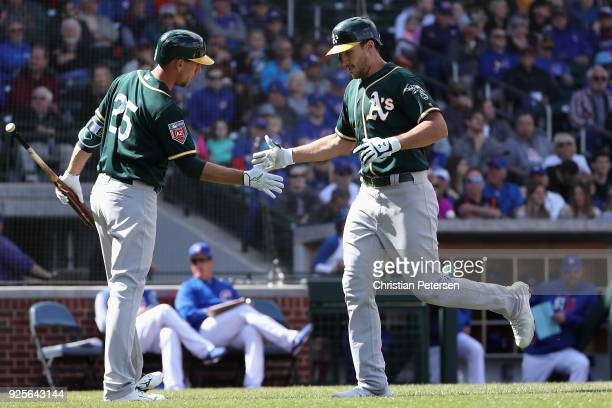 Matt Olson of the Oakland Athletics high fives Stephen Piscotty of the Oakland Athletics after hitting a solo home run against the Chicago Cubs...