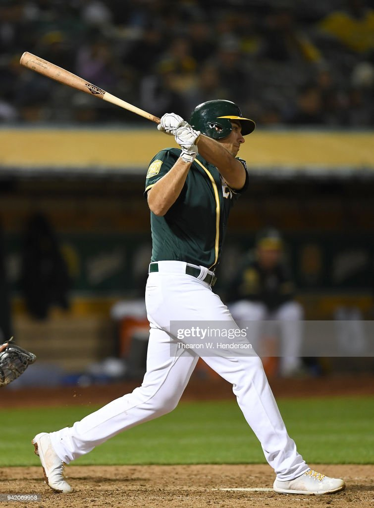 Matt Olson #28 of the Oakland Athletics hits a bases loaded rbi single scoring Matt Joyce #23 against the Texas Rangers in the bottom of the seventh inning at the Oakland Alameda Coliseum on April 4, 2018 in Oakland, California.