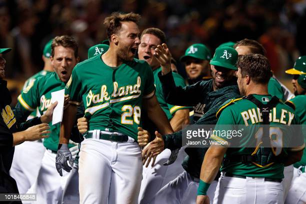 Matt Olson of the Oakland Athletics is congratulated by teammates after hitting a walk off home run against the Houston Astros during the tenth...