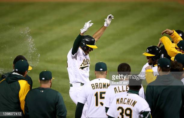 Matt Olson of the Oakland Athletics is congratulated by teammates after he hit a grand slam home run in the tenth inning to beat the Los Angeles...