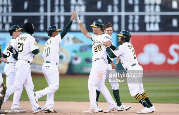 Matt Olson of the Oakland Athletics is congratulated by teammates after he hit the game winning single in the bottom of the 14th inning to beat the...