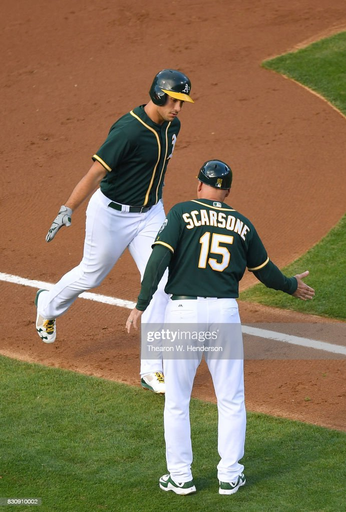 Matt Olson #28 of the Oakland Athletics is congratulated by third base coach Steve Scarsone #15 after Olson hit a solo home run against the Baltimore Orioles in the bottom of the second inning at Oakland Alameda Coliseum on August 12, 2017 in Oakland, California.