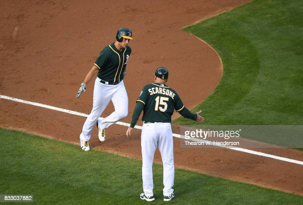 Matt Olson of the Oakland Athletics is congratulated by third base coach Steve Scarsone after Olson hit a solo home run against the Baltimore Orioles...