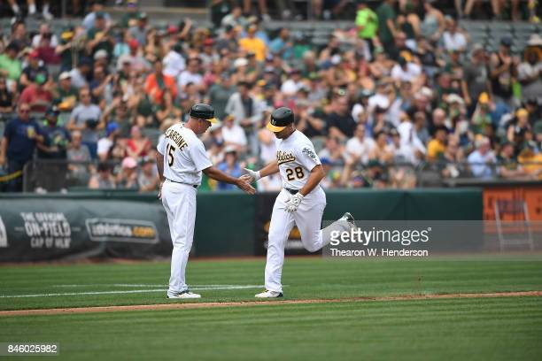 Matt Olson of the Oakland Athletics is congratulated by third base coach Steve Scarsone after Olson hit a solo home run against the Los Angeles...