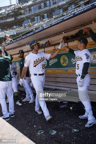 Matt Olson of the Oakland Athletics is congratulated in the dugout by Jake Smolinski after hitting a home run during the game against the Houston...