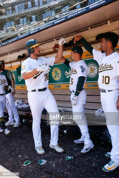 Matt Olson of the Oakland Athletics is congratulated in the dugout by Jake Smolinski and Marcus Semien after hitting a home run during the game...