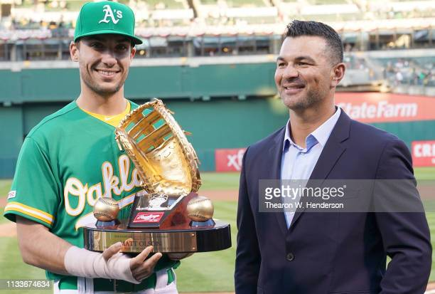 Matt Olson of the Oakland Athletics is presented with his Rawlings 2018 Gold Glove Award by former Oakland Athletics gold glover Eric Chavez prior to...
