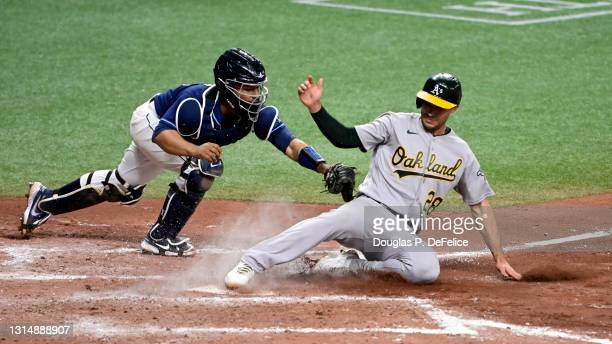 Matt Olson of the Oakland Athletics slides safely into home plate under the glove of Francisco Mejia of the Tampa Bay Rays on a sacrifice fly ball...