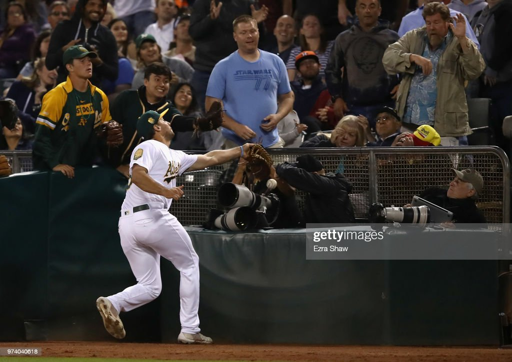 Matt Olson #28 of the Oakland Athletics tries unsuccessfully to catch a foul ball hit by Jose Altuve #27 of the Houston Astros at Oakland Alameda Coliseum on June 13, 2018 in Oakland, California.