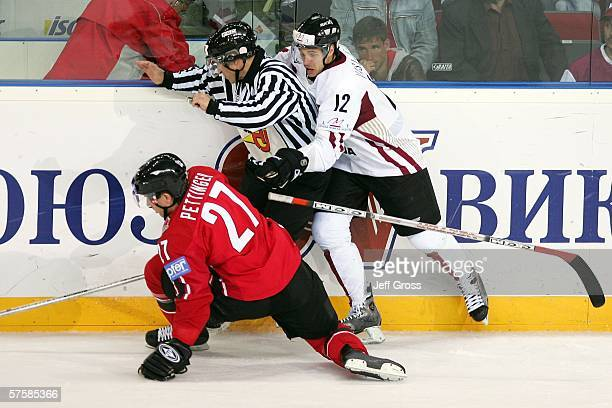 Matt Pettinger of Canada and Herberts Vasiljevs of Latvia collide with the referee during the first period of the IIHF World Championship qualifying...