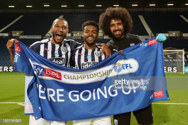Matt Phillips and Darnell Furlong of West Bromwich Albion celebrate promotion to the Premier League on the pitch at the end of the Sky Bet...