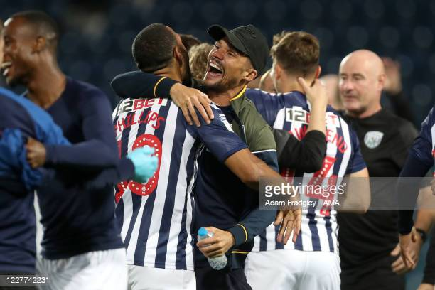 Matt Phillips and Kieran Gibbs of West Bromwich Albion embrace as they celebrate promotion to the Premier League on the pitch at the end of the Sky...