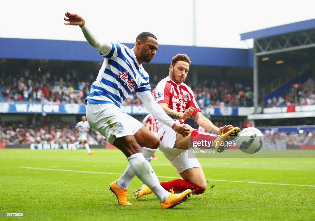 Matt Phillips of QPR is challenged by Marko Arnautovic of Stoke City during the Barclays Premier League match between Queens Park Rangers and Stoke City at Loftus Road on September 20, 2014 in London, England.