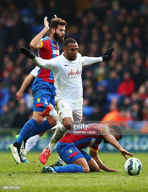 Matt Phillips of QPR is tackled by Joe Ledley and Adrian Mariappa of Crystal Palace during the Barclays Premier League match between Crystal Palace...