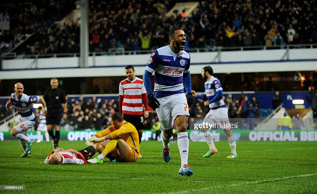 Matt Phillips of Queens Park Rangers celebrates scoring 1st goal with a dejected Ross Turnbull of Doncaster Rovers during the Sky Bet Championship match between Queens Park Rangers and Doncaster Rovers at Loftus Road on January 1, 2014 in London, England,