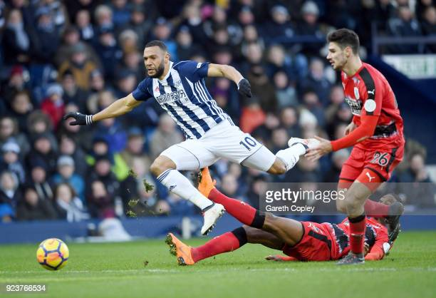 Matt Phillips of West Bromwich Albion jumps over a tackle from Terence Kongolo of Huddersfield Town during the Premier League match between West...