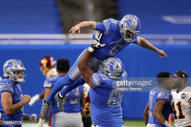Matt Prater of the Detroit Lions celebrates with his team after kicking the game-winning field goal during their game against the Washington Football...