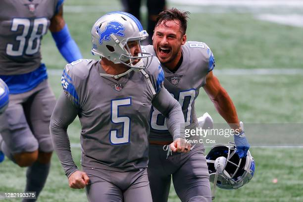 Matt Prater of the Detroit Lions is congratulated by Danny Amendola after kicking the game-winning extra point to defeat the Atlanta Falcons 23-22 at...