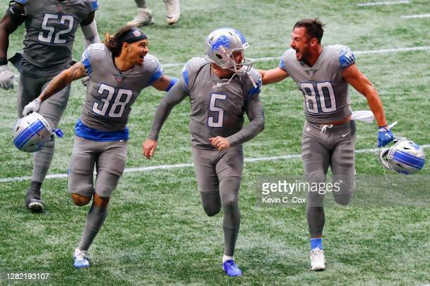 Matt Prater of the Detroit Lions is congratulated by Mike Ford and Danny Amendola after kicking the game-winning extra point to defeat the Atlanta...