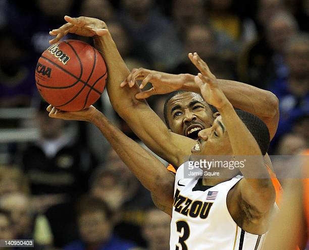 Matt Pressey of the Missouri Tigers battles Michael Cobbins of the Oklahoma State Cowboys for a rebound during the NCAA Big 12 basketball tournament...
