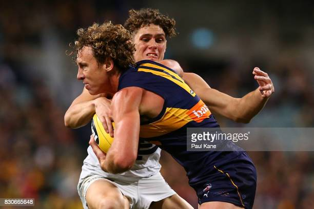 Matt Priddis of the Eagles attempts to break from a tackle by Charlie Curnow of the Blues during the round 21 AFL match between the West Coast Eagles...