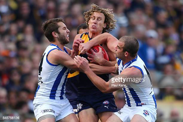 Matt Priddis of the Eagles gets tackled by Jamie Macmillan and Ben Cunnington of the Kangaroos during the round 16 AFL match between the West Coast...