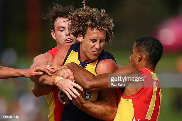 Matt Priddis of the Eagles gets tackled by Luke Russell and Touk Miller of the Suns during the 2016 AFL NAB Challenge match between the West Coast...