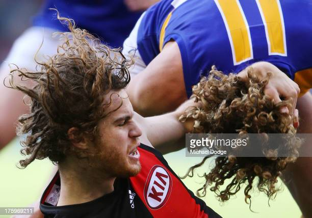 Matt Priddis of the Eagles gets tackled by Nick Kommer of the Bombers during the round 20 AFL match between the Essendon Bombers and the West Coast...
