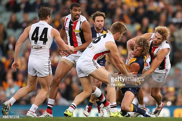 Matt Priddis of the Eagles gets tackled by Sebastian Ross and Sam Gilbert of the Saints during the round 23 AFL match between the West Coast Eagles...