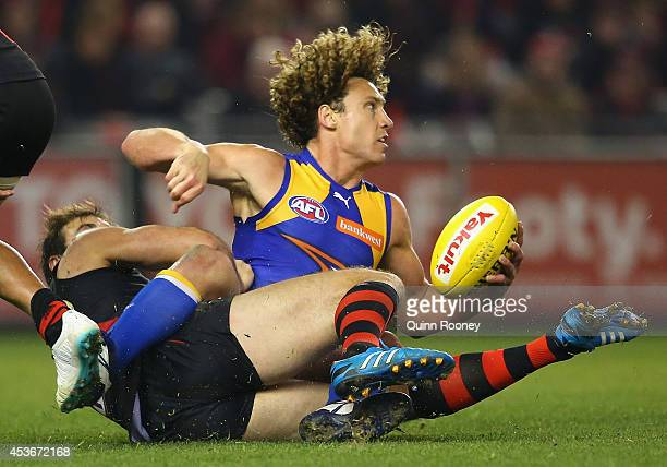 Matt Priddis of the Eagles handballs whilst being tackled by Jobe Watson of the Bombers during the round 21 AFL match between the Essendon Bombers...