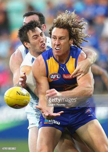 Matt Priddis of the Eagles handballs whilst being tackled by Sam Wright of the Kangaroos during the round 10 AFL match between the North Melbourne...