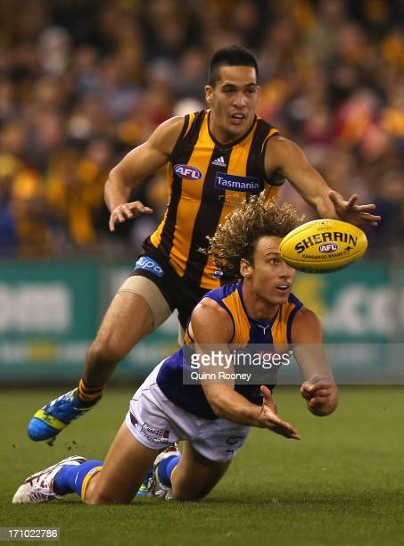 Matt Priddis of the Eagles handballs whilst being tackled by Shane Savage of the Hawks during the round 13 AFL match between the Hawthorn Hawks and...