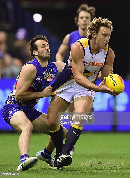 Matt Priddis of the Eagles handballs whilst being tackled Tory Dickson of the Bulldogs during the round 11 AFL match between the Western Bulldogs and...