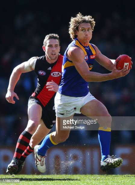 Matt Priddis of the Eagles runs with the ball away from Heath Hocking of the Bombers during the round 20 AFL match between the Essendon Bombers and...