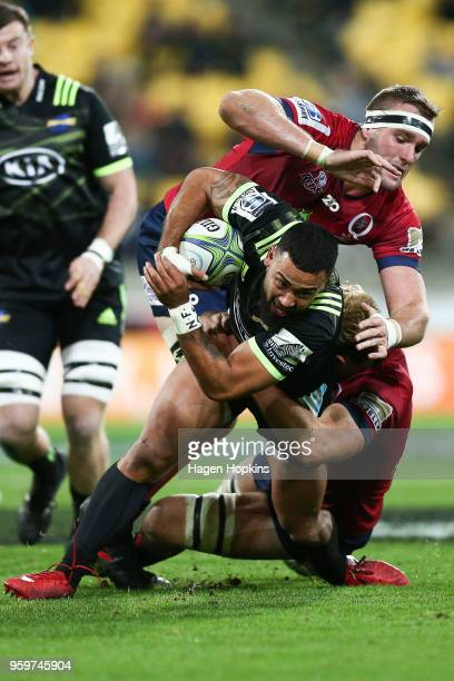 Matt Proctor of the Hurricanes is tackled by Izack Rodda and Angus ScottYoung of the Reds during the round 14 Super Rugby match between the...