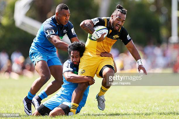 Matt Proctor of the Hurricanes is tackled by Tevita Li and Matt Vaega of the Blues during the Super Rugby preseason match between the Blues and the...
